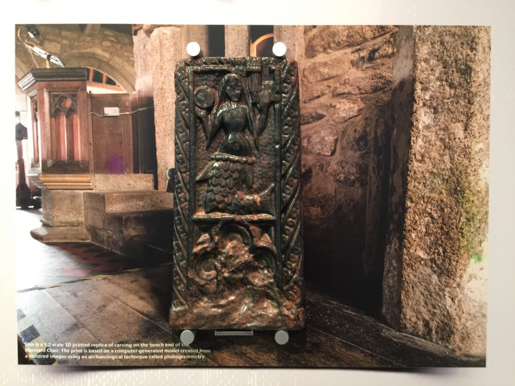 3D printed replica of the Mermaid of Zennor medieval bench end mounted over a photograph of the real bench in the church of St Senara.